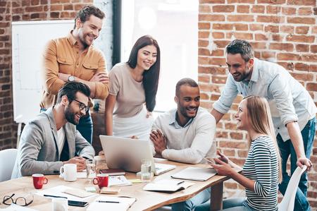Equipe bem sucedida. Grupo de jovens alegres discutindo algo com sorriso e gesticulando ao inclinar-se para a mesa no escrit�rio Imagens