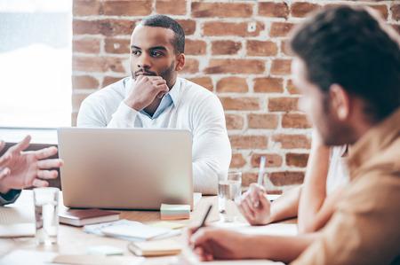 empleado de oficina: Escuchando a la nueva estrategia de negocios. Reflexivo joven africano hombre con la mano en la barbilla y escuchando mientras que sus compañeros de trabajo discutiendo algo que se sienta en la mesa de oficina