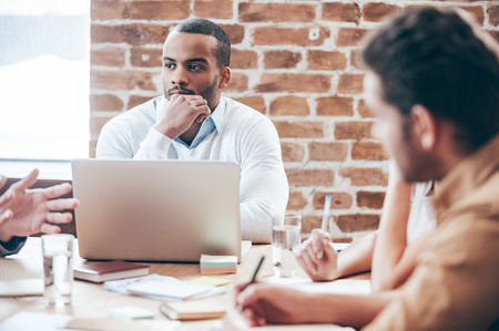 Hören neue Geschäftsstrategie. Nachdenklich junger afrikanischer Mann der Hand am Kinn halten und zu hören, während seine Mitarbeiter etwas sitzt auf dem Bürotisch diskutieren