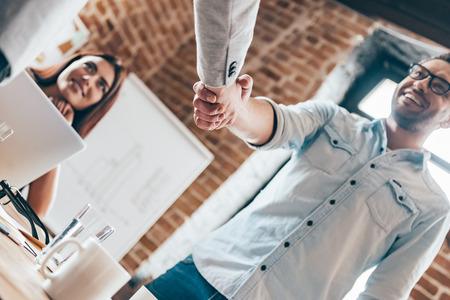 personas saludandose: �Felicitaciones! �ngulo de visi�n baja de dos hombres d�ndose la mano, mientras que su compa�ero de trabajo sentado en la mesa en la oficina