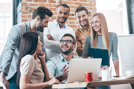 work group: Great result! Group of six young people discuss something with smile while leaning to the table in office Stock Photo