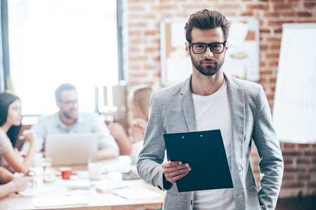 bel homme: affaires confiant. Beau jeune homme tenant bloc-notes et regardant la caméra tandis que ses collègues discuter de quelque chose dans le fond