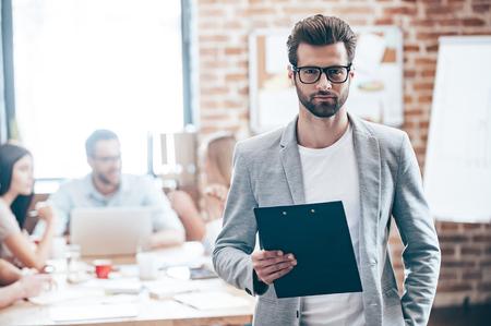 Zuversichtlich Geschäftsmann. Junger stattlicher Mann mit Notizblock und Blick in die Kamera, während seine Kollegen etwas im Hintergrund diskutieren