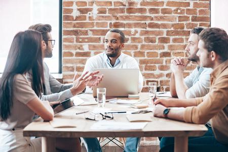 Het maken van de nieuwe strategie. Groep jonge mensen die iets bespreken tijdens de vergadering op de houten tafel in het kantoor