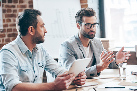 caucasian: Discussing new business strategy. Young handsome man wearing glasses gesturing and discussing something while other young man holding touchpad and listening to him sitting at the office table Stock Photo