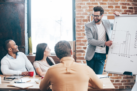 pointing at: We have some great news! Handsome young man in glasses standing near whiteboard and pointing on the chart while his coworkers listening and sitting at the table  Stock Photo