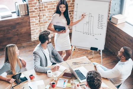 Bu rakamlara bir göz atın! güzel bir genç kadın beyaz tahta yanında duran ve onun arkadaşları ona bakarken grafik işaret ve ofiste masada oturan üstten görünümü