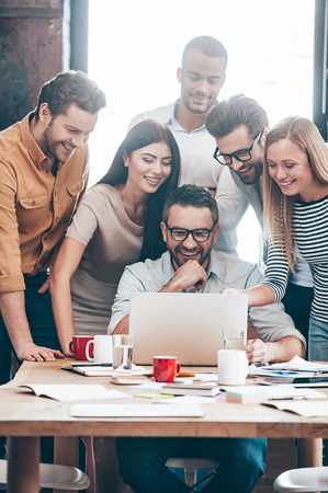 people standing: Glad with the results of their work. Group of six cheerful young business people looking at laptop and smiling while looking at laptop together