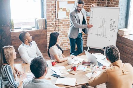 Devemos usar esta estratégia! Vista de cima do homem novo considerável nos vidros que estão perto do whiteboard e que aponta no gráfico enquanto seus colegas ouvir e sentado à mesa no escritório