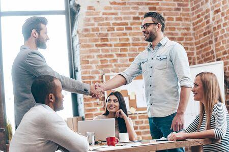 empleado de oficina: Bienvenido a nuestro equipo! Dos hombres agitando las manos y sonriendo mientras que sus compa�eros de trabajo sentado en la mesa en la oficina