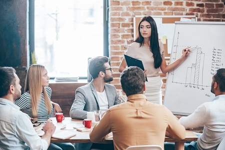 conclusions: Time to make conclusions. Beautiful young woman standing near whiteboard and pointing on the chart while her coworkers listening and sitting at the table  Stock Photo