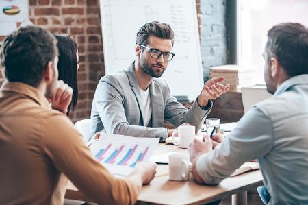 Wirtschaft diskutieren. Junger stattlicher Mann in den Brillen Gestik und etwas, während seine Mitarbeiter diskutieren, während zusammen auf dem Bürotisch sitzen Lizenzfreie Bilder