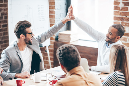 success man: We did it! Two young men doing high-five while their coworkers sitting at the office table Stock Photo