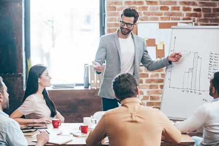 Dê uma olhada em nossos resultados! Homem novo considerável nos vidros que estão perto do whiteboard e que aponta no gráfico enquanto seus colegas ouvir e sentado à mesa