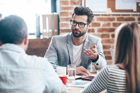 Tiempo para discutir nuestros planes de negocio. Hombre hermoso joven que llevaba gafas gesticulando y hablando de algo, mientras que sus compañeros de trabajo que lo escuchaban sentados en la mesa de la oficina Foto de archivo