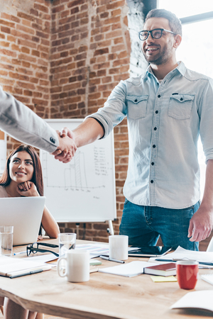 casual office: Welcome on board! Two businessmen shaking hands while standing near office table Stock Photo