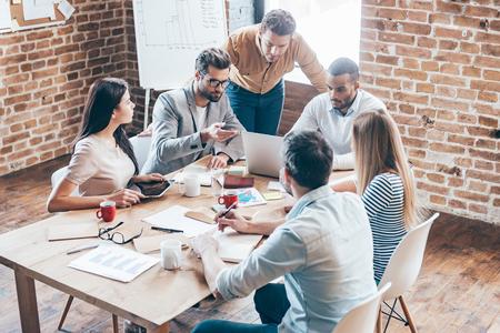 Trabajando como equipo. Grupo de seis jóvenes discutiendo algo y hacer gestos mientras está sentado en la mesa en la oficina