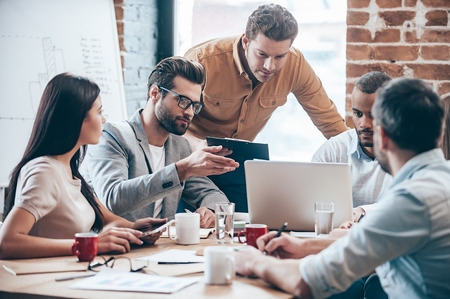 group: Concentrated at work. Group of five young people discuss something and gesturing while leaning to the table in office Stock Photo
