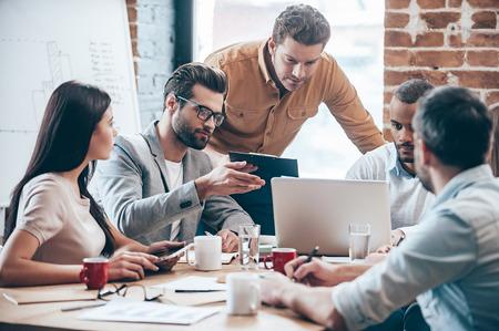 Konzentriert bei der Arbeit. Gruppe von fünf jungen Menschen diskutieren etwas und Gestik während im Büro an den Tisch gelehnt