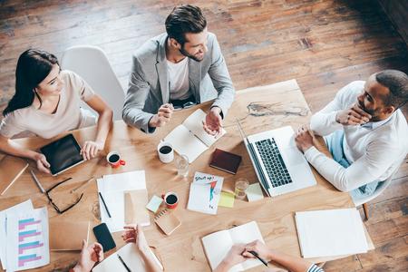 la comunicación del equipo. Vista superior parte del grupo de cinco personas discutiendo algo con sonrisa mientras está sentado en la mesa de oficina