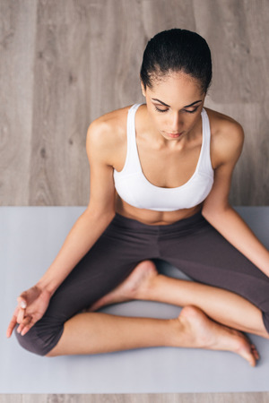 mat like: Feel all the energy inside you. Top view of beautiful young African woman in sportswear practicing yoga while sitting in lotus position on the floor