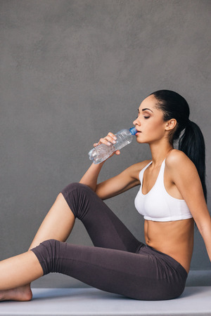sip: Sip of water after good workout. Side view of beautiful young African woman in sportswear drinking water while sitting on exercise mat against grey background