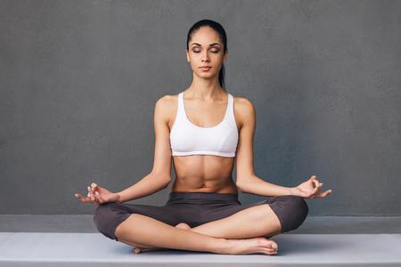 lotus position: Long breath in. Beautiful young African woman in sportswear practicing yoga while sitting in lotus position against grey background Stock Photo