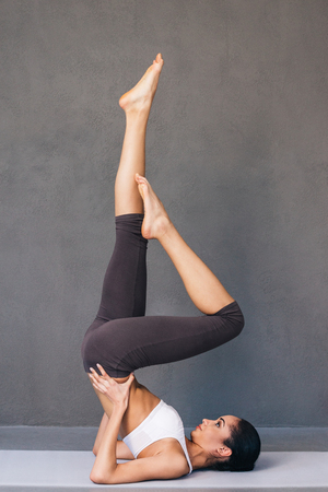 mat like: Strong and graceful. Side view of beautiful young African woman in sportswear practicing yoga on exercise mat against grey background
