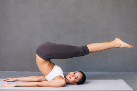 stretchy: Stretchy beauty. Side view of beautiful young African woman in sportswear practicing yoga and looking at camera with smile while lying on exercise mat against grey background Stock Photo