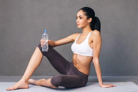 buena postura: Buen entrenamiento para un buen cuerpo. Vista lateral de la mujer africana hermosa joven en ropa deportiva con una botella de agua y mirando a otro lado mientras está sentado en la estera del ejercicio contra el fondo gris Foto de archivo