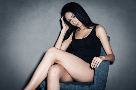 sex pose: Flirty in chair. Beautiful young African woman in black swimsuit looking at camera and keeping legs crossed at knees while sitting in chair against grey background