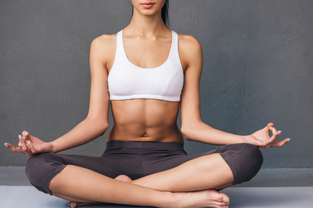 sports clothing: Stay calm. Close-up part of young African woman in sportswear practicing yoga while sitting in lotus position against grey background Stock Photo