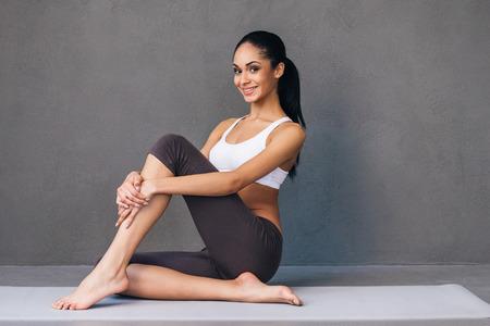 buena postura: belleza deportiva y en forma. mujer africana joven hermosa en ropa deportiva mirando a la cámara con una sonrisa mientras está sentado en la estera del ejercicio contra el fondo gris