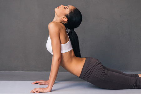 mat like: Upward facing dog. Side view of beautiful young African woman in sportswear practicing yoga on exercise mat against grey background
