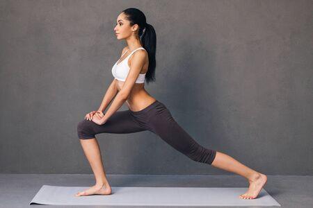 buena postura: Guerrero. Vista lateral de la mujer africana hermosa joven en ropa deportiva que practica yoga en la estera del ejercicio contra el fondo gris Foto de archivo