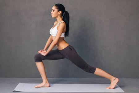 Warrior. Side view of beautiful young African woman in sportswear practicing yoga on exercise mat against grey background