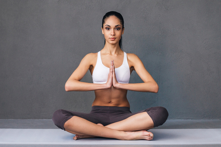 namaste: Namaste! Beautiful young African woman in sportswear practicing yoga and looking at camera while sitting in lotus position against grey background