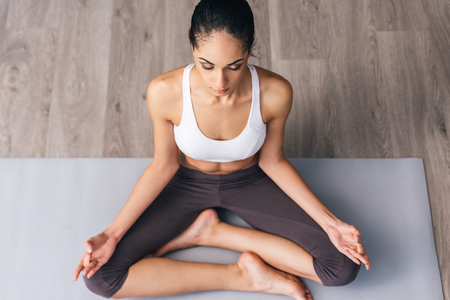 women sitting: Concentration and meditation. Top view of beautiful young African woman in sportswear practicing yoga while sitting in lotus position on the floor