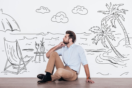 hand on chin: Dreaming about vacation. Young handsome man keeping hand on chin and looking away while sitting on the floor with illustration of resort in the background