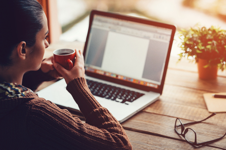 female form: Morning inspiration. Close-up image of pensive young woman holding coffee cup and looking away while sitting at her working place at the rough wooden table