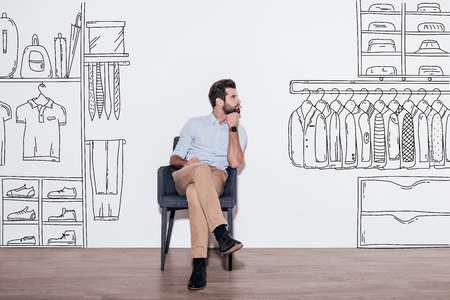 man t shirt: Dreaming about new wardrobe. Young handsome man keeping hand on chin and looking away while sitting in the chair against illustration of closet in the background Stock Photo