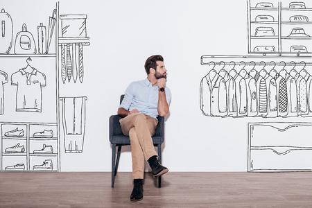 guay: Sueño sobre nuevo guardarropa. El hombre hermoso joven que guarda la mano en la barbilla y mirando a otro lado mientras se está sentado en la silla contra la ilustración de armario en el fondo Foto de archivo