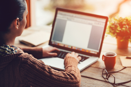 自宅で仕事。大まかな木製テーブルに座ってラップトップに取り組んでいる若い女性のクローズ アップ画像 写真素材
