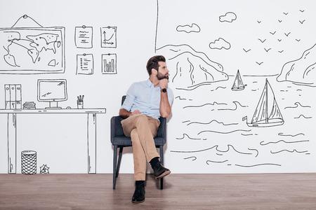 Seus sonhos podem enviar-lhe longe. Homem considerável novo mantendo a mão no queixo e olhando para longe, sentado na cadeira contra a ilustração do fjord vs. local de trabalho