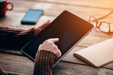 work table: Opening the world with single touch. Close-up image of young woman holding digital tablet with copy space while sitting at the rough wooden table