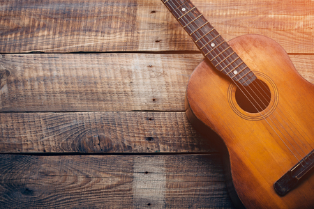 sound music: Wooden guitar. Close-up of guitar lying on vintage wood background