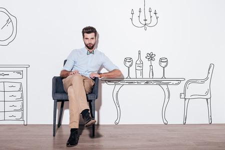 이 표. 젊은 잘 생긴 남자 유지 다리 건너와 백그라운드에서 식탁의 그림에 대해 의자에 앉아있는 동안 카메라를보고