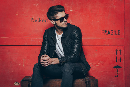 Gorgeous and stylish. Handsome young man in sunglasses keeping hands clasped and looking away while sitting on wooden chest against red background