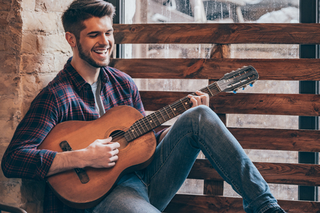 windowsill: Cheerful guitarist. Cheerful handsome young man playing guitar and smiling while sitting at windowsill