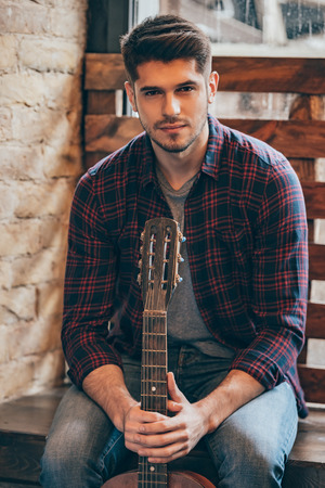 sitting man: Handsome musician. Handsome young man holding guitar and looking at camera while sitting at windowsill Stock Photo